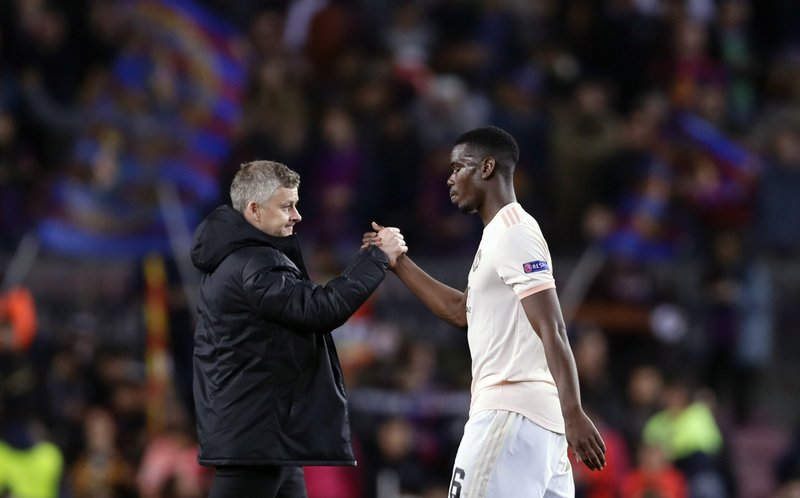 Manchester United coach Ole Gunnar Solskjaer, left, shakes hands with Manchester United's Paul Pogba at the end of the Champions League quarterfinal, second leg, soccer match between FC Barcelona and Manchester United at the Camp Nou stadium in Barcelona, Spain, Tuesday, April 16, 2019. (AP Photo/Manu Fernandez)