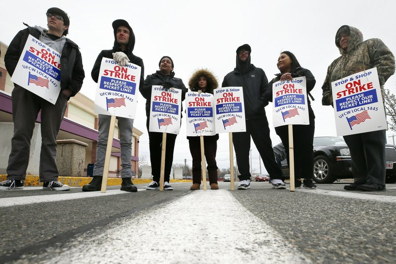 Striking workers stand on a picket line outside the Stop & Shop supermarket in Revere, Mass., Thursday, April 18, 2019. (AP Photo/Michael Dwyer)