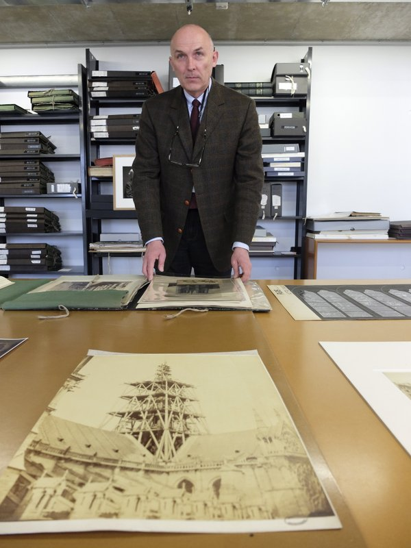 Jean-Charles Forgeret poses with archives documents related to Notre Dame cathedral in Charenton le Pont, outside Paris, Thursday, April 18, 2019. (AP Photo/Nicolas Garriga)