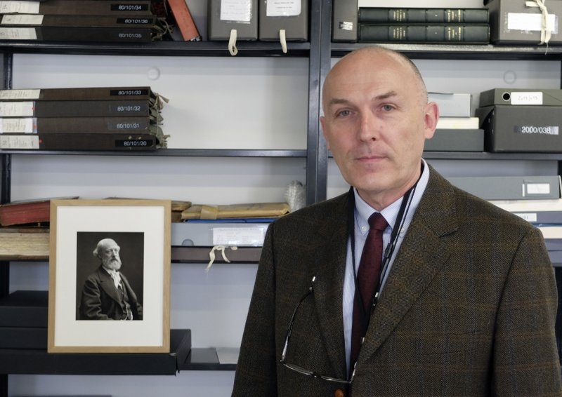 Jean-Charles Forgeret poses next to photograph of Eugene Emmanuel Viollet-le-Duc, the renowned architect who designed the spire that was added to the medieval cathedral in the 19th century, in Charenton le Pont, outside Paris, Thursday, April 18, 2019. (AP Photo/Nicolas Garriga)