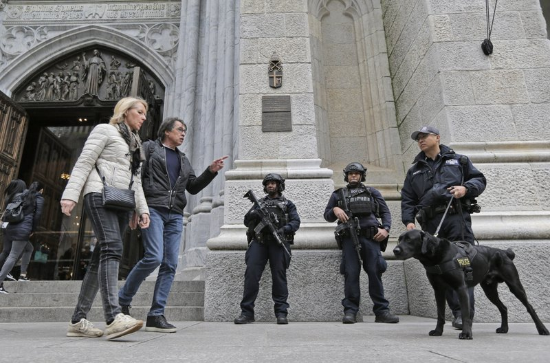 Tourists walk past police officers standing in front of St. Patrick's Cathedral in New York, Thursday, April 18, 2019. (AP Photo/Seth Wenig)
