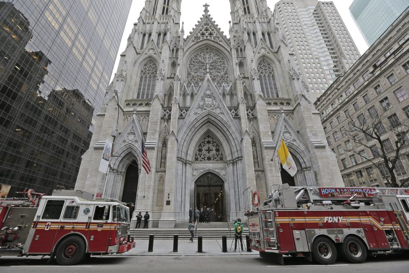While firemen conduct an inspection, fire trucks are parked in front of St. Patrick's Cathedral in New York, Thursday, April 18, 2019. (AP Photo/Seth Wenig)