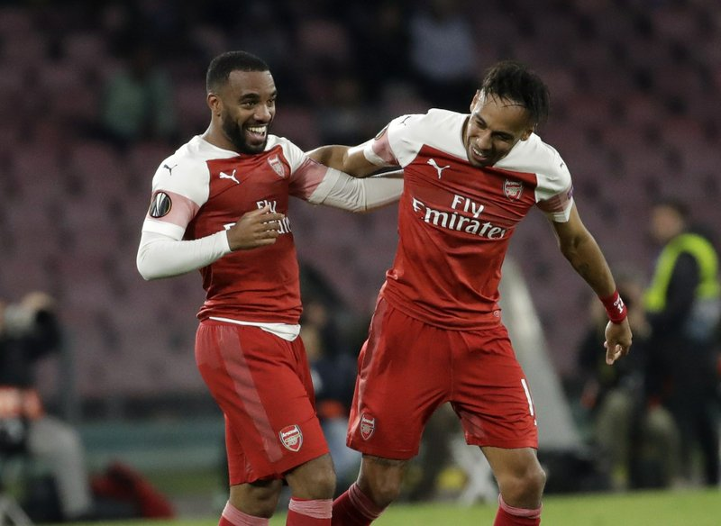 Arsenal's Alexandre Lacazette, left, celebrates after scoring his side's first goal during the Europa League second leg quarterfinal soccer match between Napoli and Arsenal at San Paolo stadium in Naples, Italy, Thursday, April 18, 2019. (AP Photo/Luca Bruno)
