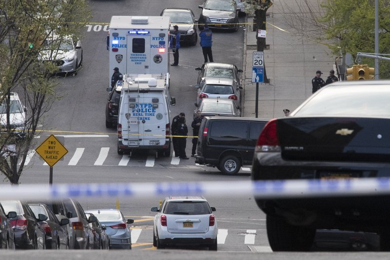 Emergency service personnel work at the scene where a police officer has been shot in the arm and a suspect has been killed during a police shooting in New York, Thursday, April 18, 2019. (AP Photo/Mary Altaffer)