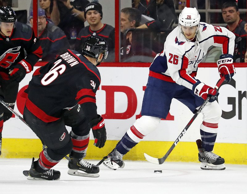 Washington Capitals' Nic Dowd (26) moves the puck as Carolina Hurricanes' Patrick Brown (36) defends during the first period of Game 4 of an NHL hockey first-round playoff series in Raleigh, N. (AP Photo/Karl B DeBlaker)
