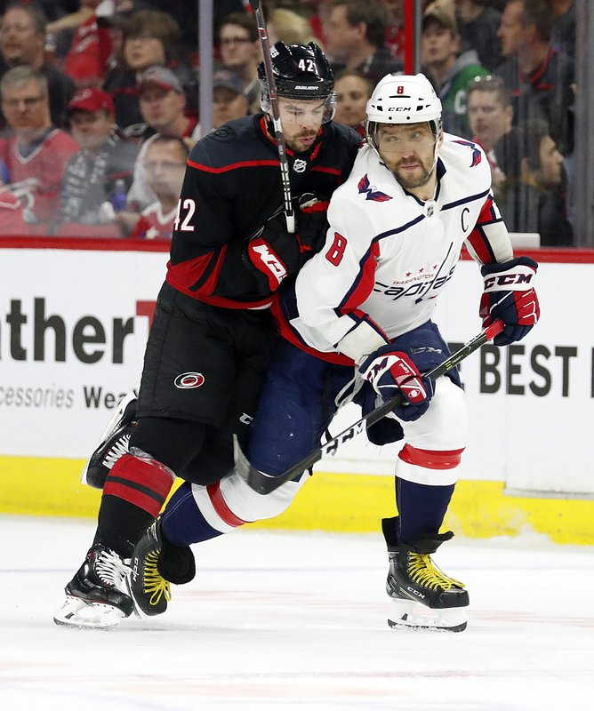Washington Capitals' Alex Ovechkin (8), of Russia, tangles with Carolina Hurricanes' Greg McKegg (42) during the first period of Game 4 of an NHL hockey first-round playoff series in Raleigh, N. (AP Photo/Karl B DeBlaker)