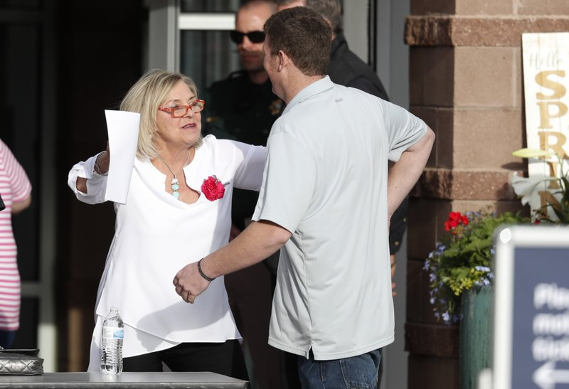 Beth Woydziak, left, reaches out to hug an attendee arriving at a faith-based memorial service for the victims of the massacre at Columbine High School nearly 20 years earlier, at a community church, Thursday, April 18, 2019, in Littleton, Colo. (AP Photo/David Zalubowski)