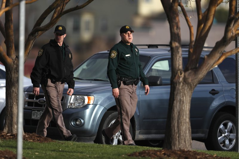 Jefferson County Sheriff's Department deputies walk the parking lot as participants arrive to attend a faith-based memorial service for the victims of the massacre at Columbine High School nearly 20 years ago at a community church Thursday, April 18, 2019, in Littleton, Colo. (AP Photo/David Zalubowski)