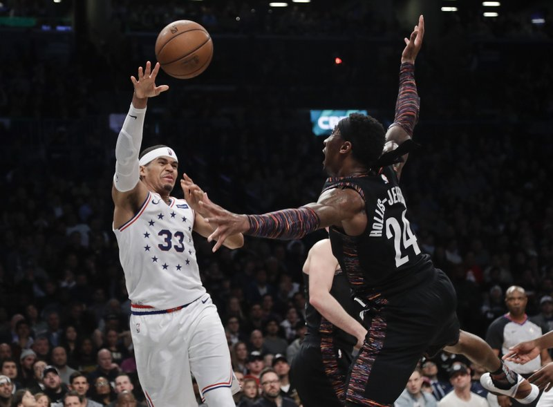 Philadelphia 76ers' Tobias Harris (33) passes away from Brooklyn Nets' Rondae Hollis-Jefferson (24) during the second half in Game 3 of a first-round NBA basketball playoff series Thursday, April 18, 2019, in New York. (AP Photo/Frank Franklin II)