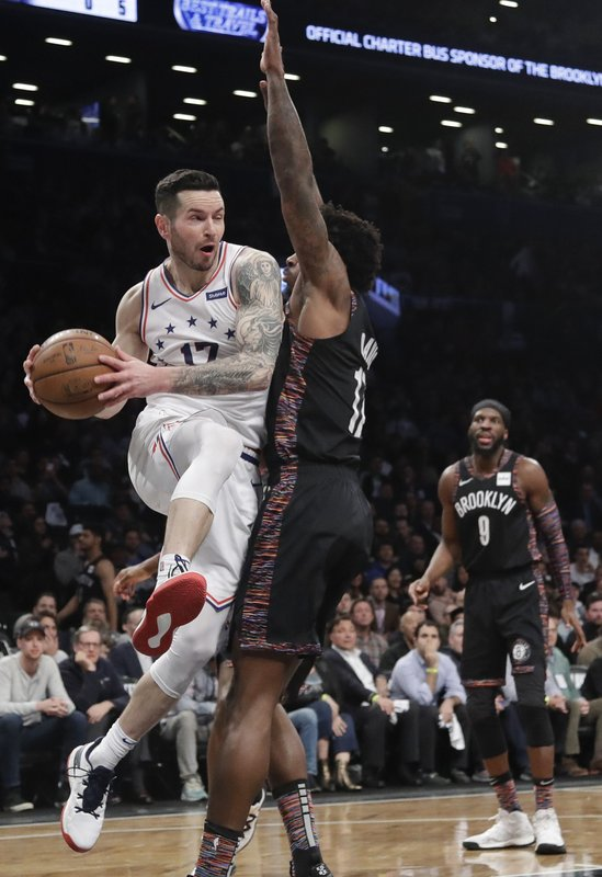 Philadelphia 76ers' JJ Redick (17) looks to pass the ball away from Brooklyn Nets' Ed Davis (17) during the first half in Game 3 of a first-round NBA basketball playoff series Thursday, April 18, 2019, in New York. (AP Photo/Frank Franklin II)