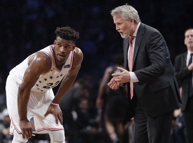 Philadelphia 76ers coach Brett Brown, right, talks to Jimmy Butler during the first half in Game 3 of the team's first-round NBA basketball playoff series against the Brooklyn Nets on Thursday, April 18, 2019, in New York. (AP Photo/Frank Franklin II)