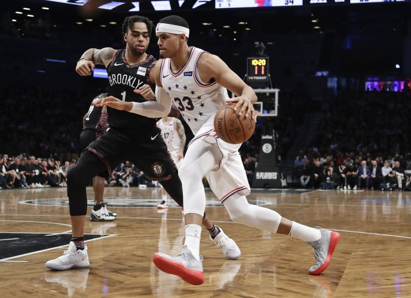 Philadelphia 76ers' Tobias Harris (33) drives past Brooklyn Nets' D'Angelo Russell (1) during the first half in Game 3 of a first-round NBA basketball playoff series Thursday, April 18, 2019, in New York. (AP Photo/Frank Franklin II)