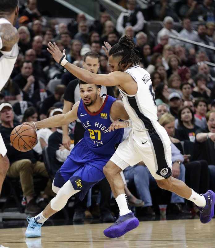 Denver Nuggets guard Jamal Murray (27) drives around San Antonio Spurs guard Patty Mills (8) during the first half of Game 3 of an NBA basketball playoff series in San Antonio, Thursday, April 18, 2019. (AP Photo/Eric Gay)