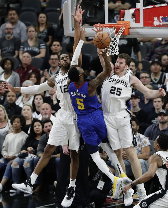 Denver Nuggets guard Will Barton (5) tries to score against San Antonio Spurs center LaMarcus Aldridge (12) and center Jakob Poeltl (25) during the first half of Game 3 of an NBA basketball playoff series in San Antonio, Thursday, April 18, 2019. (AP Photo/Eric Gay)