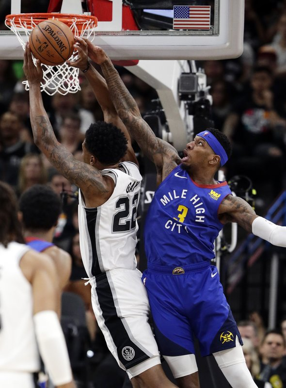 Denver Nuggets forward Torrey Craig (3) fouls San Antonio Spurs forward Rudy Gay (22) as he tries to block the shot during the first half of Game 3 of an NBA basketball playoff series in San Antonio, Thursday, April 18, 2019. (AP Photo/Eric Gay)