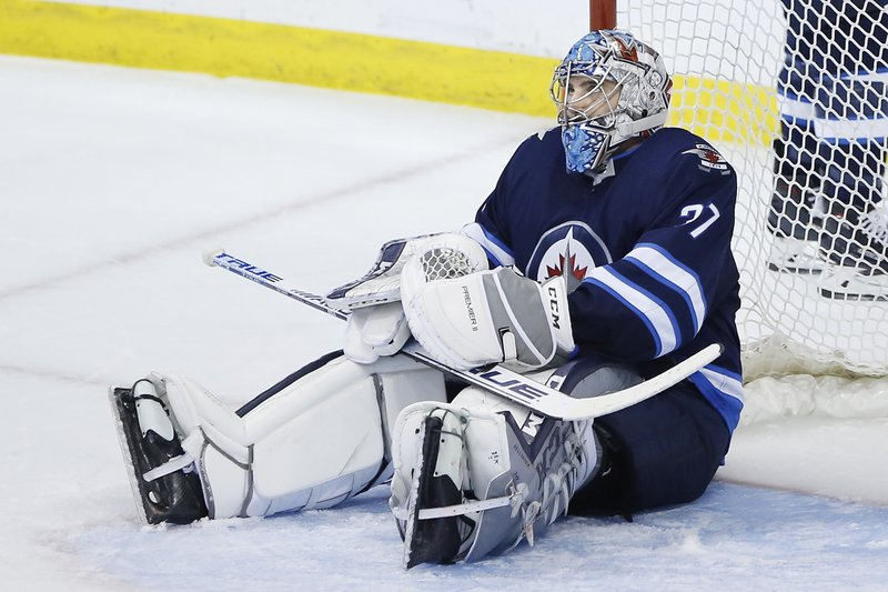 Winnipeg Jets goaltender Connor Hellebuyck reacts after St. Louis Blues' Jaden Schwartz scored in the final minute of Game 5 of an NHL hockey first-round playoff series Thursday, April 18, 2019, in Winnipeg, Manitoba. (John Woods/The Canadian Press via AP)