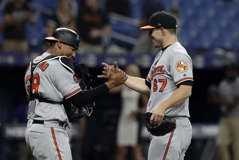 Baltimore Orioles pitcher John Means (67) celebrates with catcher Pedro Severino after closing out the Tampa Bay Rays during the 11th inning of a baseball game Thursday, April 18, 2019, in St. (AP Photo/Chris O'Meara)