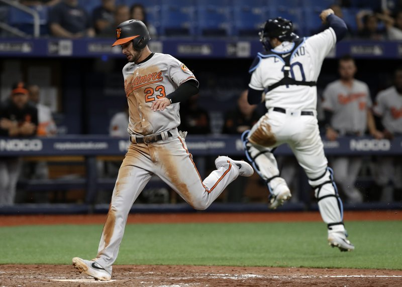 Baltimore Orioles' Joey Rickard (23) scores on a single by Richie Martin as Tampa Bay Rays catcher Mike Zunino (10) leaps for a high throw during the seventh inning of a baseball game Thursday, April 18, 2019, in St. (AP Photo/Chris O'Meara)