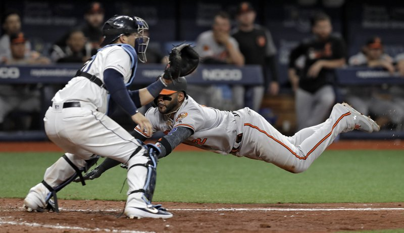 Baltimore Orioles' Jonathan Villar, right, goes airborne as he scores in front of Tampa Bay Rays catcher Mike Zunino on a sacrifice fly by Dwight Smith Jr. (AP Photo/Chris O'Meara)