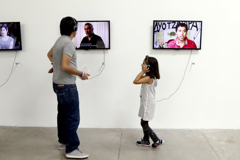 People listen to video portraits of family members of the 43 college students who went missing in an apparent 2014 massacre, and experts on the case, at an art exhibit titled