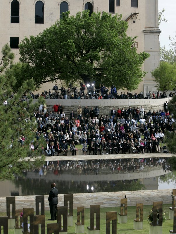 FILE - In this April 19, 2010 file photo, people gather under the Survivor Tree at the Oklahoma City National Memorial during a ceremony marking the 15th anniversary of the Oklahoma City bombing. (AP Photo/Sue Ogrocki, File)