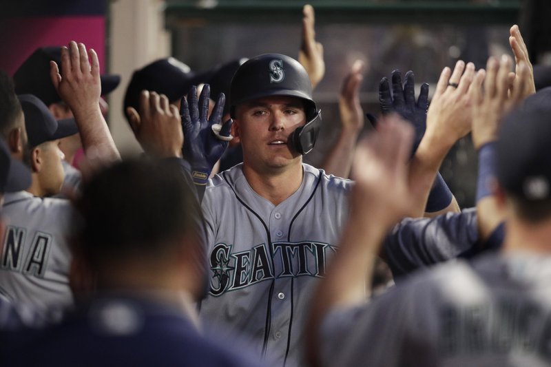 Seattle Mariners' Ryon Healy, center, is greeted by teammates after hitting a thee-run home run during the second inning of a baseball game against the Los Angeles Angels on Thursday, April 18, 2019, in Anaheim, Calif. (AP Photo/Jae C. Hong)