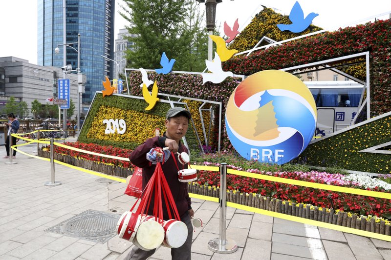A man selling Chinese drums walk past a decoration promoting the upcoming Road and Belt Forum in Beijing on Friday, April 19, 2019. (AP Photo/Ng Han Guan)