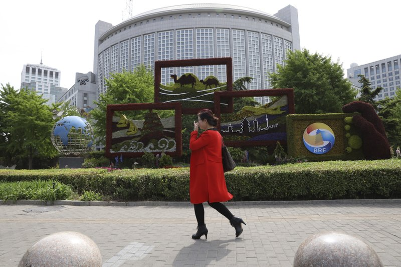 A woman walks past a decoration promoting the upcoming Road and Belt Forum outside the Chinese Foreign Ministry in Beijing on Friday, April 19, 2019. (AP Photo/Ng Han Guan)