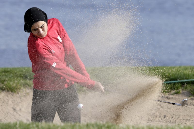 In this April 10, 2019 photo, Noor Ahmed, a member of the Nebraska NCAA college golf team, hits out of a sand trap during practice in Lincoln, Neb. (AP Photo/Nati Harnik)
