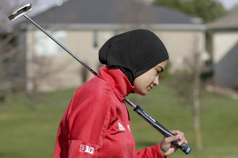 In this April 10, 2019 photo, Noor Ahmed, a member of the Nebraska NCAA college golf team, carries her putter during practice in Lincoln, Neb. (AP Photo/Nati Harnik)