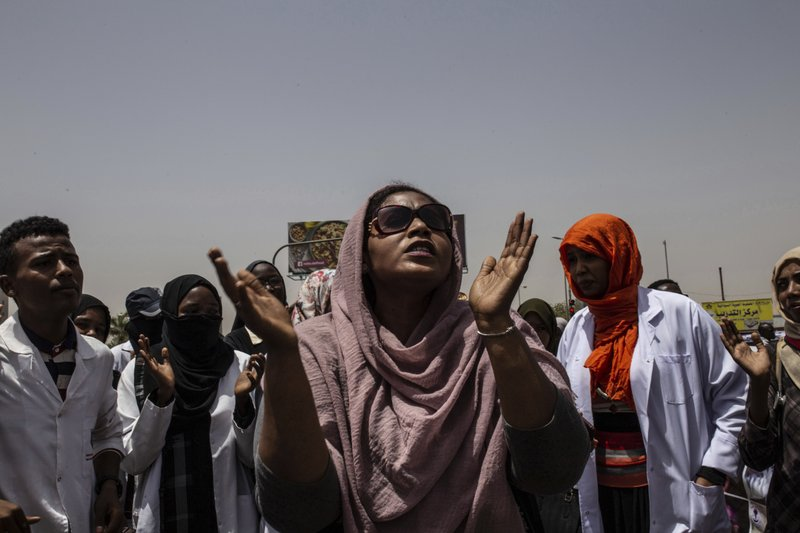 A group of protesters from the Sudanese medical profession syndicate march chant against military rule and demand prosecution for former government officials, at the sit-in inside the Armed Forces Square, in Khartoum, Sudan, Wednesday, April 17, 2019. (AP Photos/Salih Basheer)