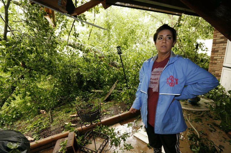 Sonya Banes reacts to a large oak tree that crashed through the patio of her mother's house in Learned, Miss. (AP Photo/Rogelio V. Solis)