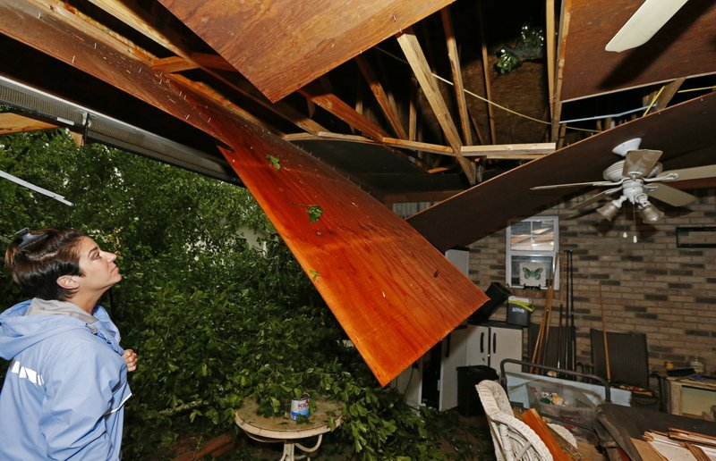 Sonya Banes looks at damage caused by a large oak tree that crashed through the ceiling of her mother's house in Learned, Miss. (AP Photo/Rogelio V. Solis)