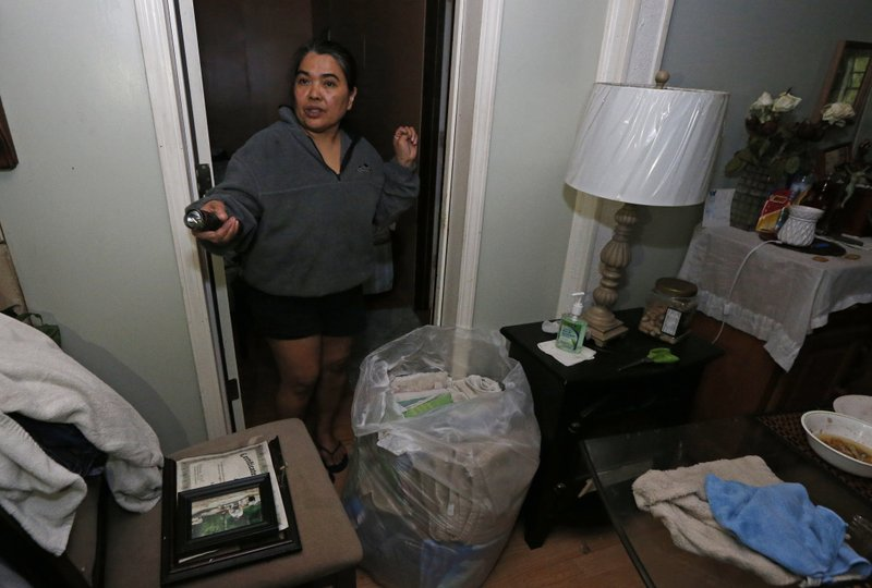 Josephinne Qualls calls to her daughter as she tries to salvage her clothes in the tree-damaged Learned, Miss. (AP Photo/Rogelio V. Solis)