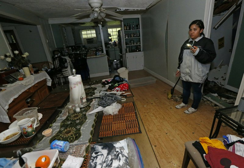 Jacqualynn Qualls calls to her mother in the tree-damaged living room of their Learned, Miss., home, following severe weather that hit the small community, Thursday, April 18, 2019. (AP Photo/Rogelio V. Solis)