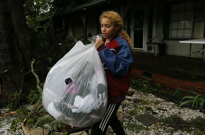 Hannah Claire carries out the unsoiled clothes of her friend Jacqualynn Qualls whose house was severely damaged by a fallen tree following severe weather that hit the small community of Learned, Miss. (AP Photo/Rogelio V. Solis)