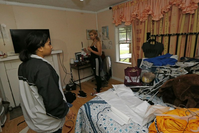 Jacqualynn Qualls, left, gathers her clothes from her undamaged room in her Learned, Miss., home, Thursday, April 18, 2019, after a oak tree demolished her brother's room, bathroom and much of the living quarters. (AP Photo/Rogelio V. Solis)
