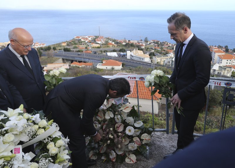 German Foreign Minister Heiko Maas, right, and Portuguese Foreign Minister Augusto Santos Silva, left, assist in laying a wreath near the scene where a bus crashed in Canico, on Portugal's Madeira Island, Thursday April 18, 2019. (AP Photo/Armando Franca)
