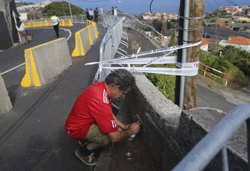 A man lights a candle on the side of the road near where a bus crashed into a house below in Canico, on Portugal's Madeira Island, Thursday April 18, 2019. (AP Photo/Armando Franca)