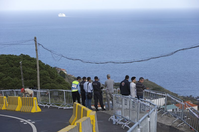 Police officers stand on the curve in the road where a bus went over the edge and crashed into a house below in Canico, on Portugal's Madeira Island, Thursday April 18, 2019. (AP Photo/Armando Franca)