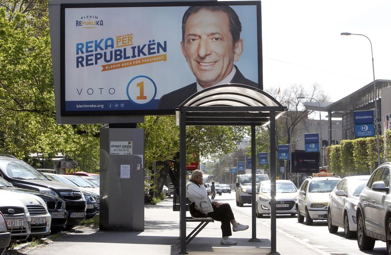 A man waits for a bus by an election poster of Blerim Reka, a candidate for two smaller ethnic Albanian opposition parties, with the inscription in Albanian reading