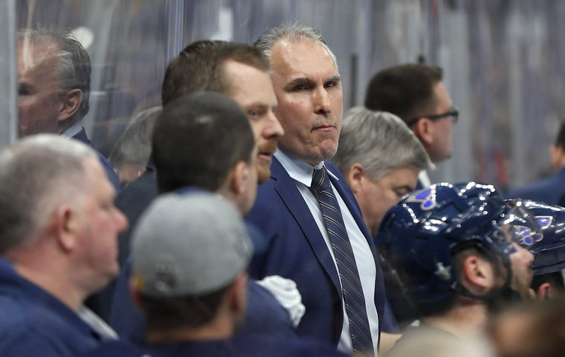 St. Louis Blues interim head coach Craig Berube, center, watches from the bench during the second period in Game 4 of an NHL first-round hockey playoff series against the Winnipeg Jets, Tuesday, April 16, 2019, in St. (AP Photo/Jeff Roberson)