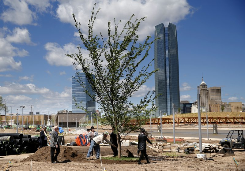 Dignitaries put dirt on a Survivor Tree clone after it was transplanted on the grounds Scissortail Park in Oklahoma City, Friday, April 19, 2019. (Sarah Phipps/The Oklahoman via AP)