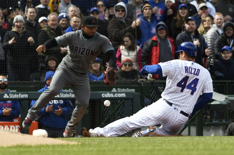 Chicago Cubs' Anthony Rizzo (44) slides safely into third base with a one-run triple as Arizona Diamondbacks third baseman Eduardo Escobar takes a late throw during the fourth inning of a baseball game, Friday, April 19, 2019, in Chicago. (AP Photo/David Banks)