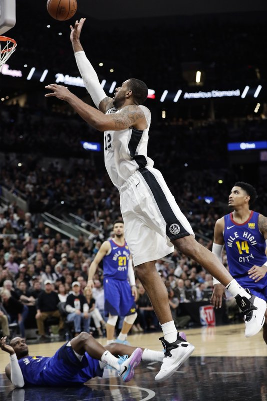 San Antonio Spurs center LaMarcus Aldridge (12) shoots over Denver Nuggets forward Paul Millsap, on court, during the first half of Game 3 of an NBA basketball playoff series in San Antonio, Thursday, April 18, 2019. (AP Photo/Eric Gay)