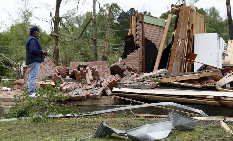 A friend of the owner reviews the remains of a storm damaged house in Morton, Miss., Friday, April 19, 2019, following a possible tornado touchdown Thursday afternoon, as strong storms again roared across the South on Thursday, topping trees and leaving a variety of damage in Mississippi, Louisiana and Texas. (AP Photo/Rogelio V. Solis)