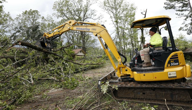 Terrill Harvey, right, uses his heavy machinery to remove debris from a friend's home, Friday, April 19, 2019, in Morton, Miss. (AP Photo/Rogelio V. Solis)