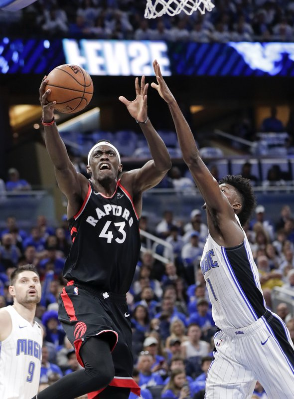 Toronto Raptors' Pascal Siakam (43) shoots against Orlando Magic's Nikola Vucevic (9) and Jonathan Isaac, right, during the first half in Game 3 of a first-round NBA basketball playoff series, Friday, April 19, 2019, in Orlando, Fla. (AP Photo/John Raoux)