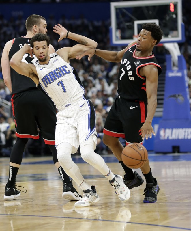 Orlando Magic's Michael Carter-Williams, left, and Toronto Raptors' Kyle Lowry collide during the first half in Game 3 of a first-round NBA basketball playoff series, Friday, April 19, 2019, in Orlando, Fla. (AP Photo/John Raoux)