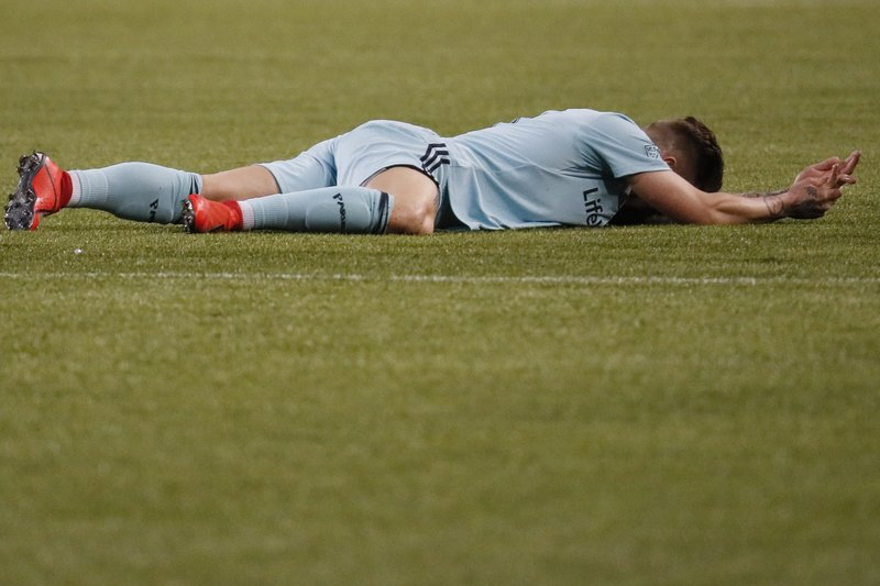 Real Salt Lake midfielder Albert Rusnak lies on the pitch after sustaining a hand injury during the first half of the team's MLS soccer match against FC Cincinnati, Friday, April 19, 2019, in Cincinnati. (AP Photo/John Minchillo)